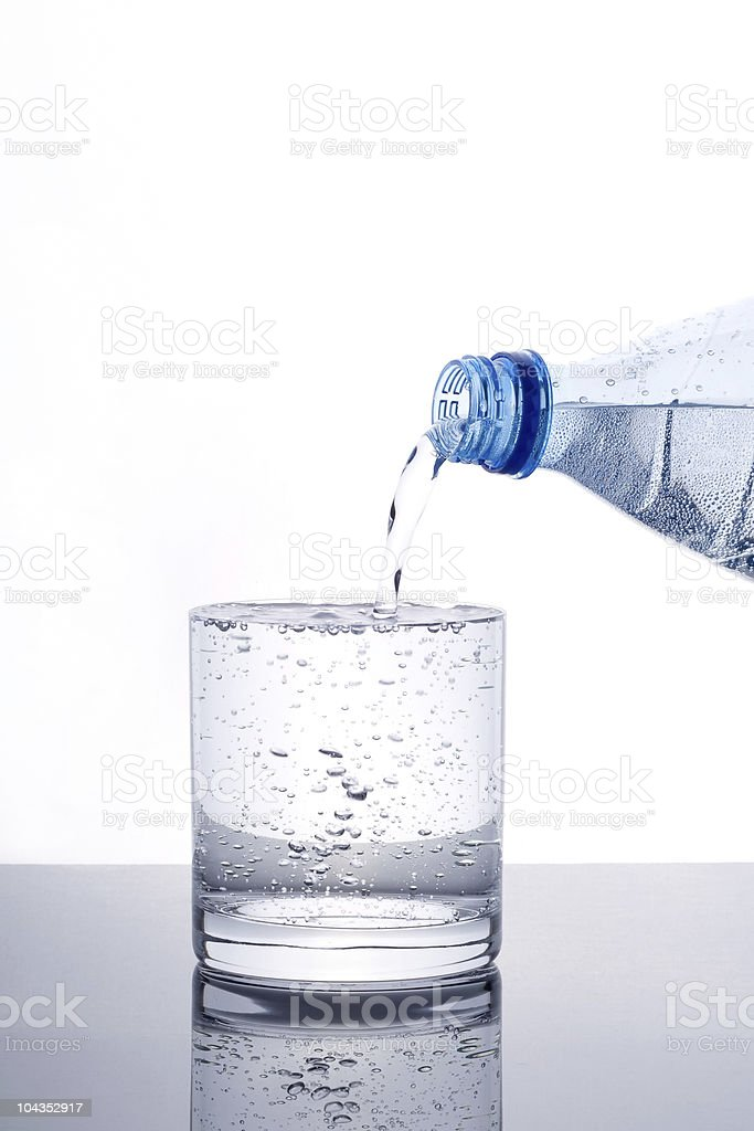 Glass of water being filled from bottle royalty-free stock photo