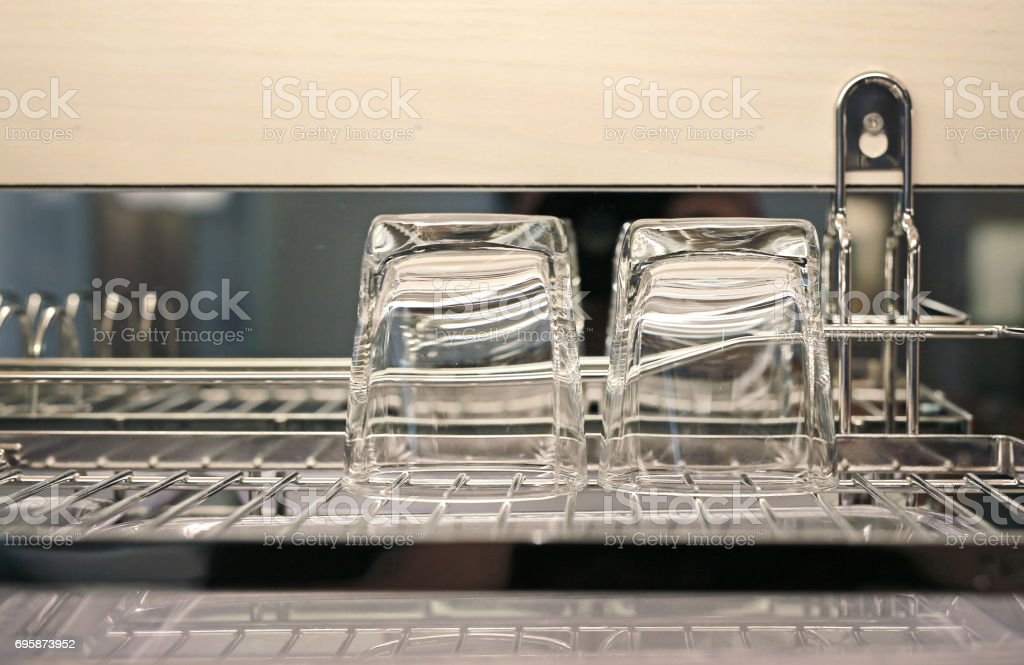Glass of water dry on stainless shelves. Glass of water turned upside down. stock photo