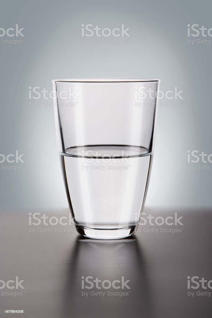 Glass of water, is it half full or half empty? stock photo