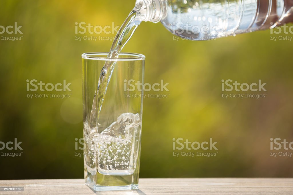 A glass of water is pouring into the glass, on the nature stock photo