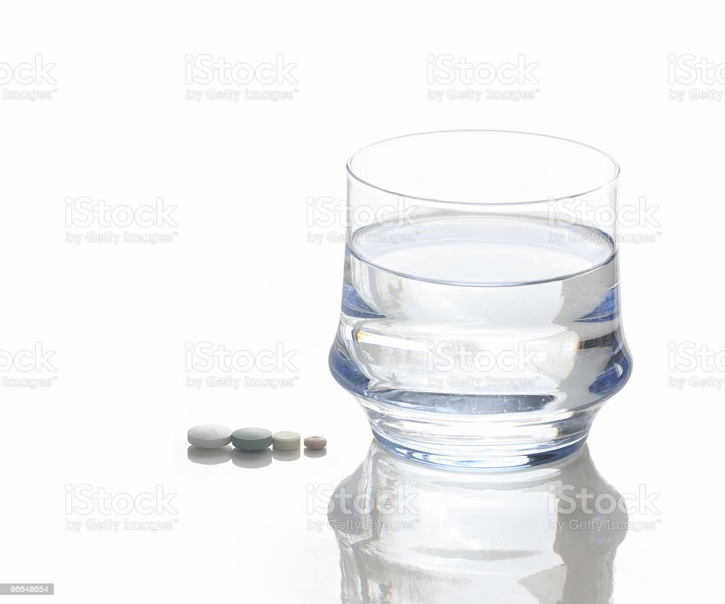 glass of water with four pills royalty-free stock photo
