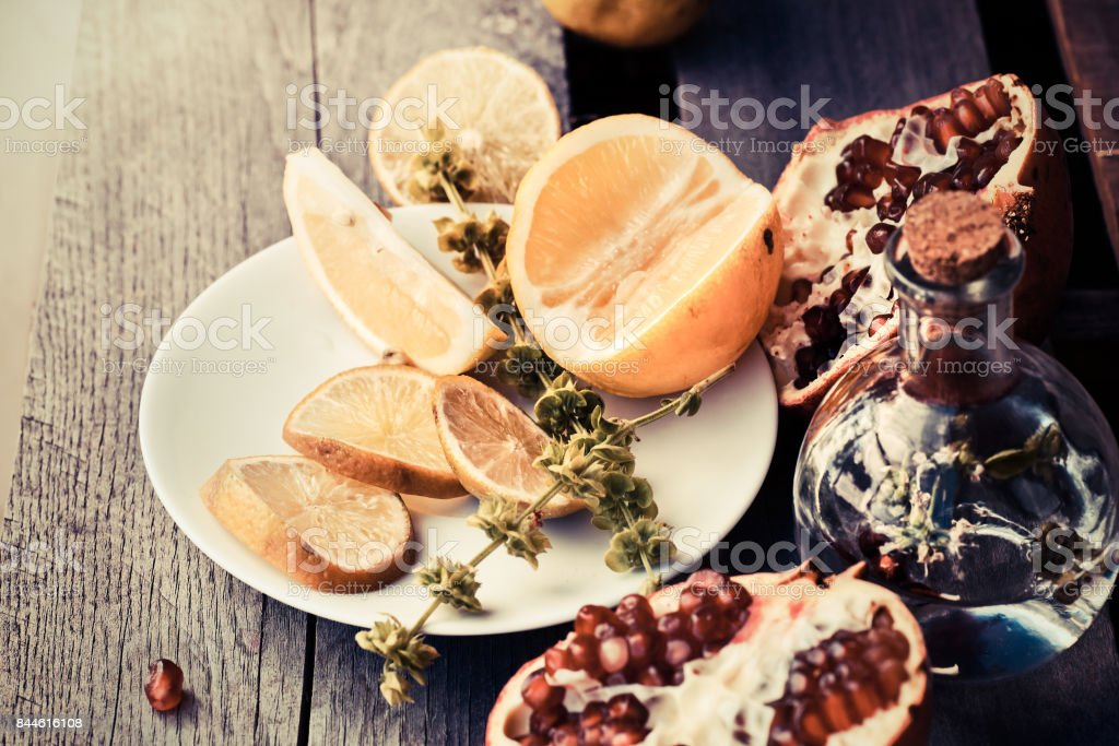 glass of water with lemonade drink with fresh citrus fruits and pomegranate on wooden board stock photo