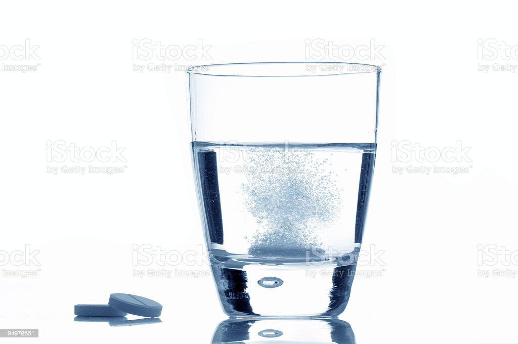 Glass of water with two tablets next to it royalty-free stock photo