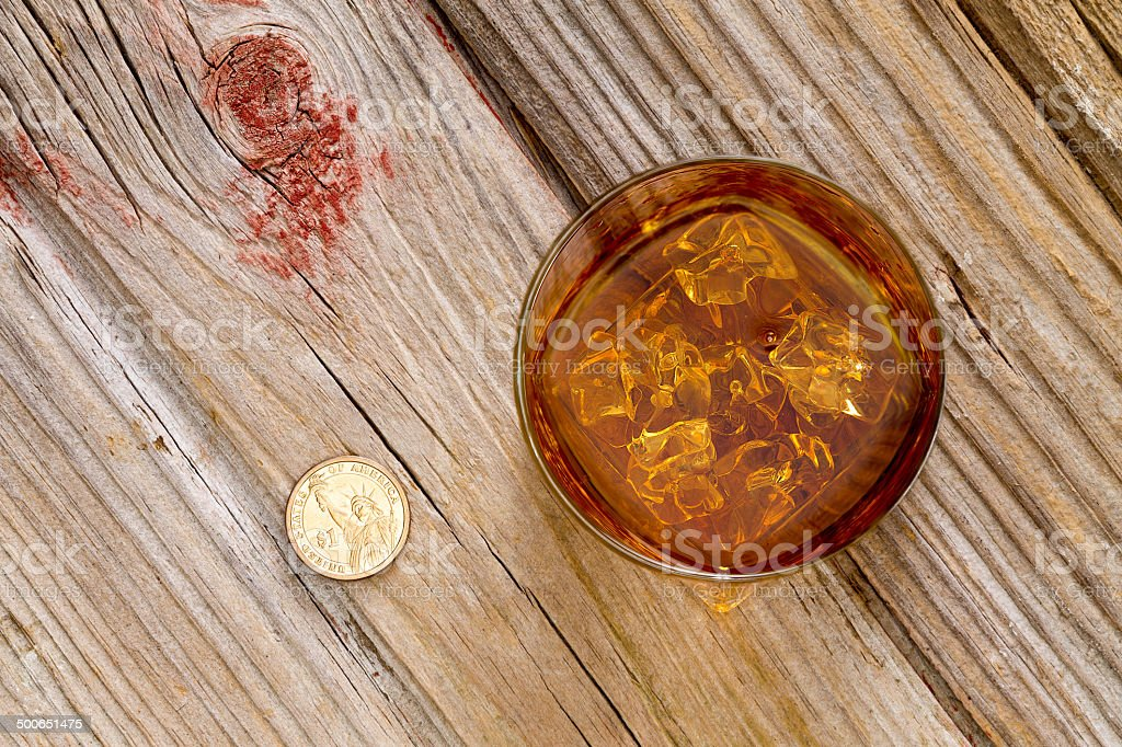 Glass of whiskey and a coin on a bar counter stock photo