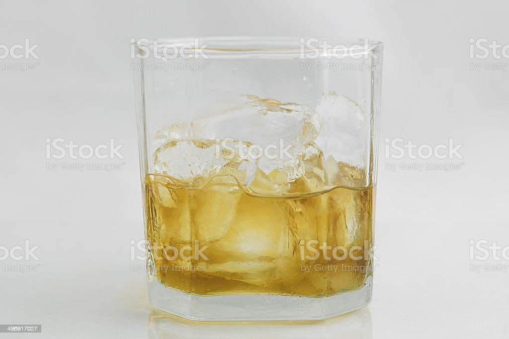 Glass of whiskey and ice on a white background stock photo
