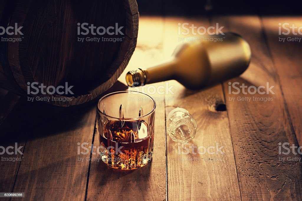 Glass of whiskey, bottle and wooden barrel stock photo