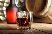 Glass of whiskey, bottle and wooden barrel