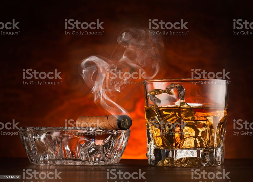 Glass of whiskey ice and cigar on wooden surface stock photo