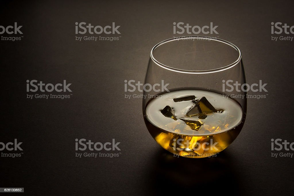 glass of whiskey on a dark background stock photo