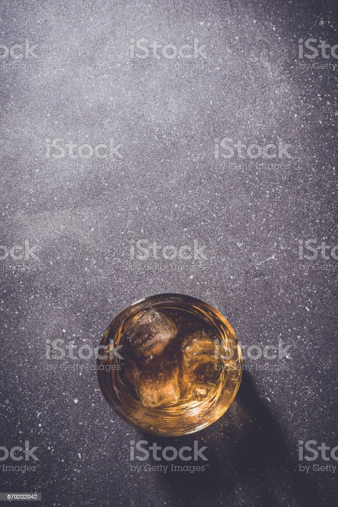 Glass of whiskey on gray stone background. stock photo