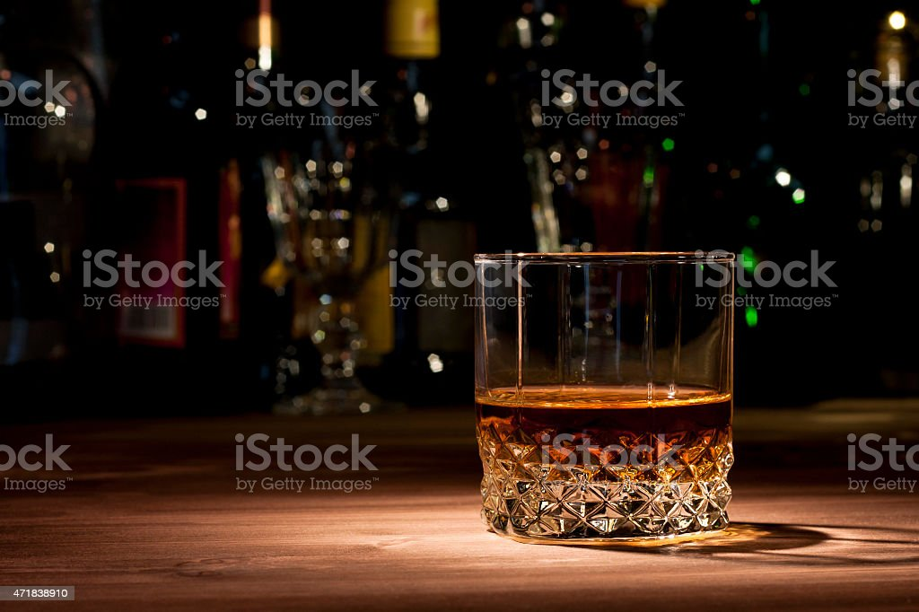 Glass of whiskey on wood with bottles in background stock photo