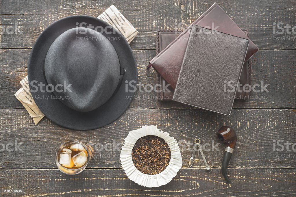 Glass of whiskey , pipe  , hat  and newspaper on wooden table stock photo