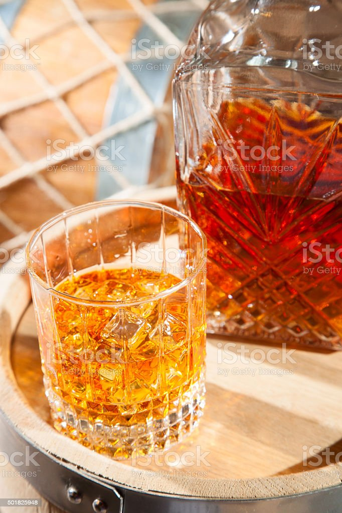 Glass of whiskey with ice and a decanter stock photo