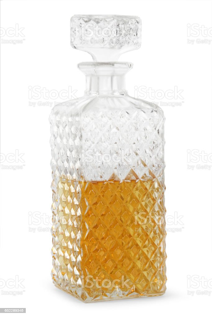 Glass of whiskey with ice and a square decanter stock photo