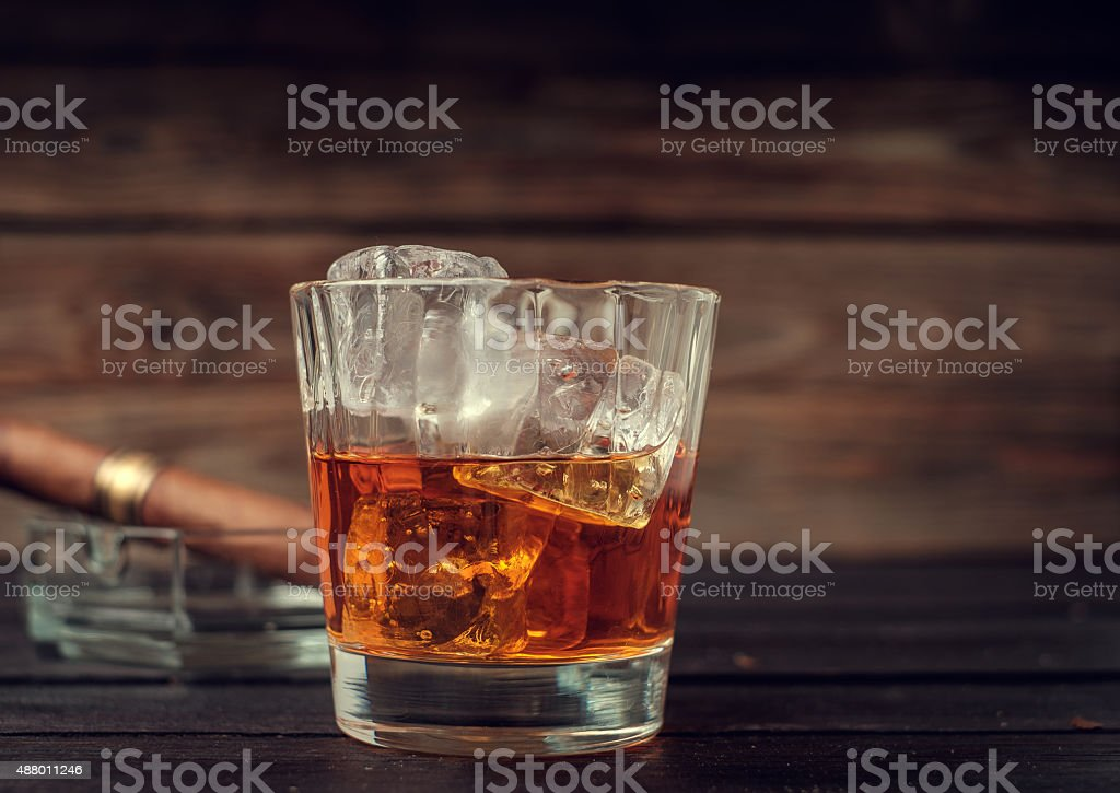 Glass of whiskey with ice and cigar stock photo