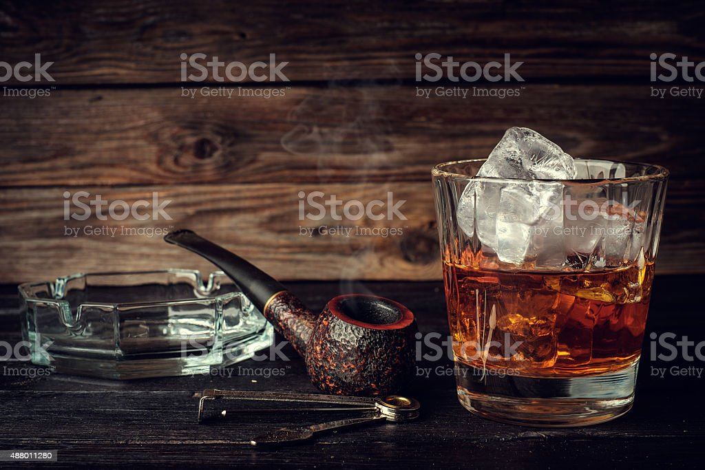 Glass of whiskey with ice and pipe stock photo