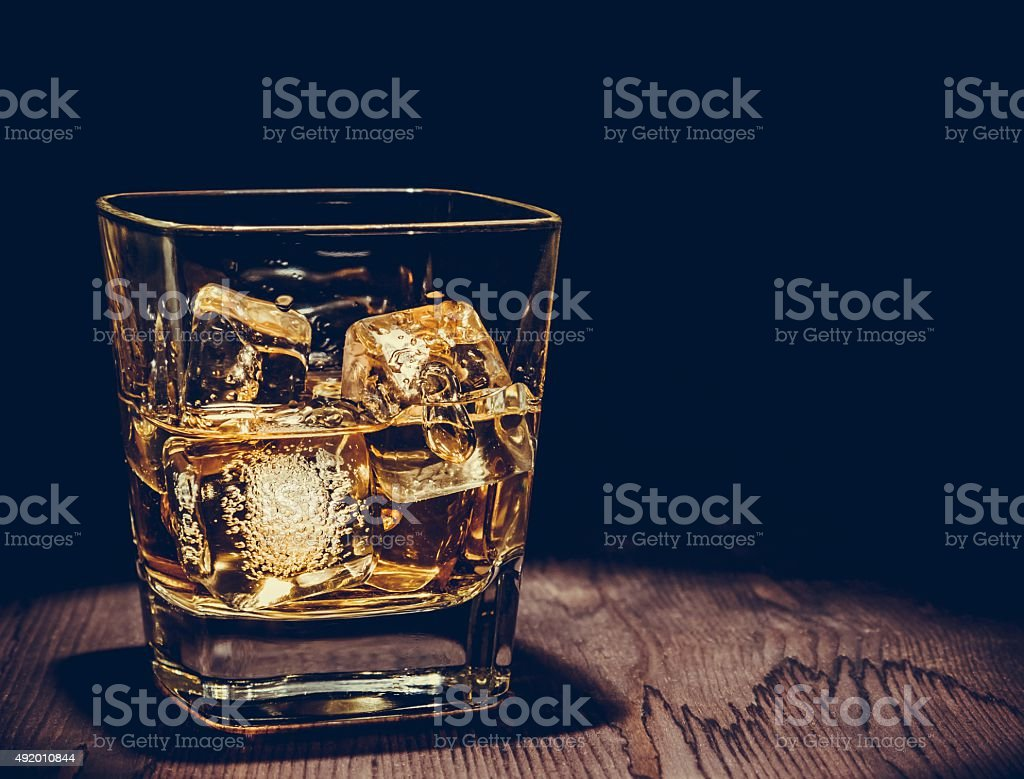 glass of whiskey with ice cubes on wood table stock photo