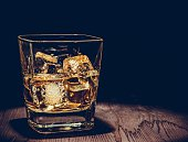 glass of whiskey with ice cubes on wood table