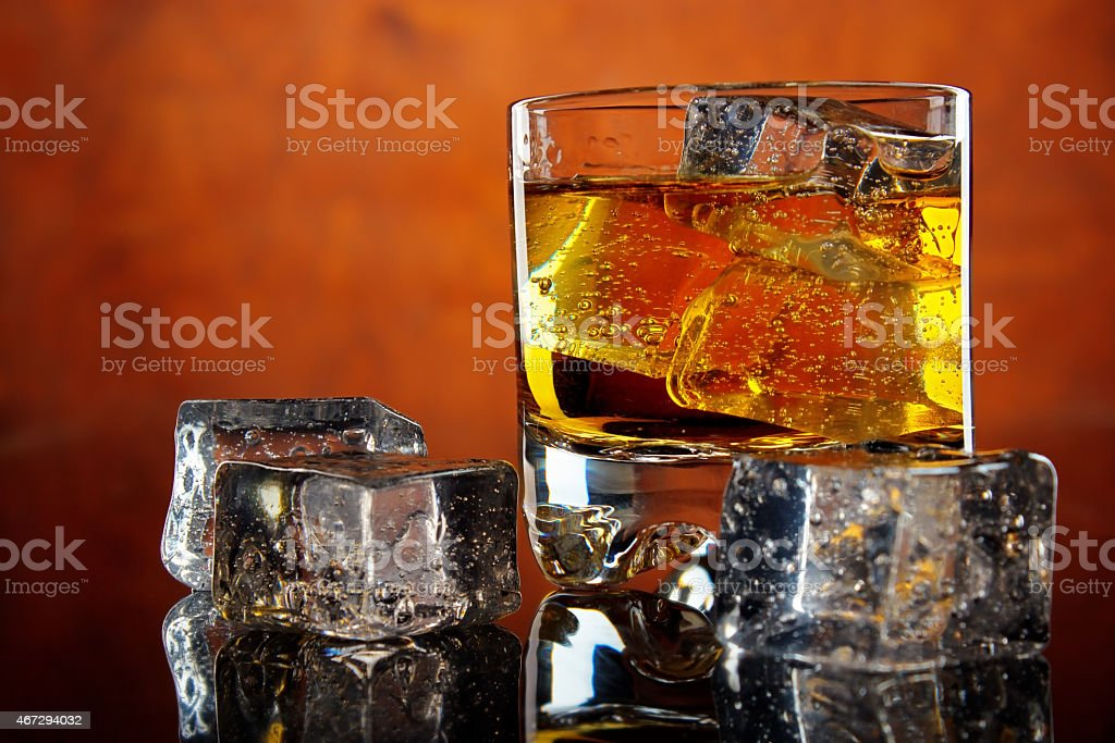 Glass of whiskey with ice cubes royalty-free stock photo