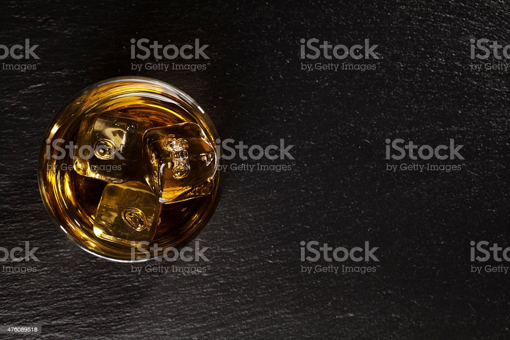 Glass of whiskey with ice on black stone stock photo