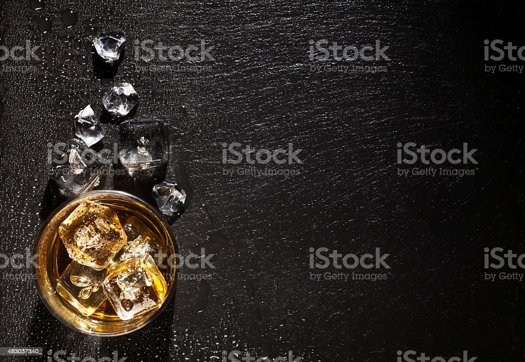 Glass of whiskey with ice on black stone table stock photo