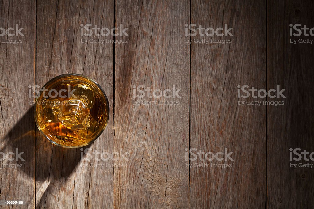 Glass of whiskey with ice on wood stock photo