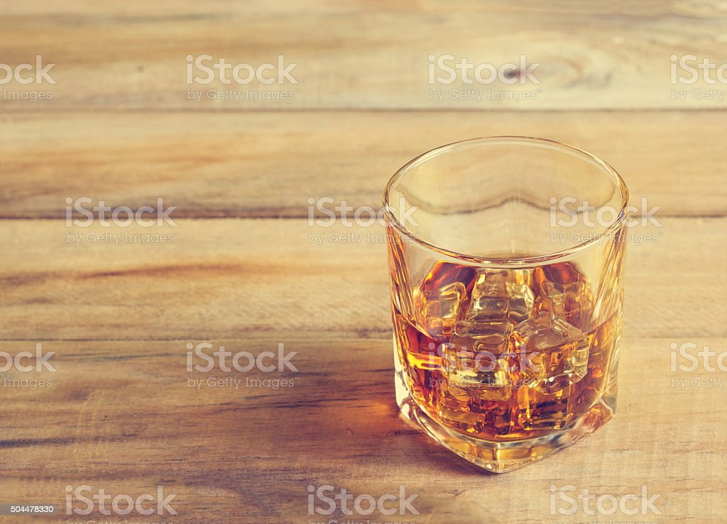 Glass of whiskey with ice on wooden background, Vintage color stock photo