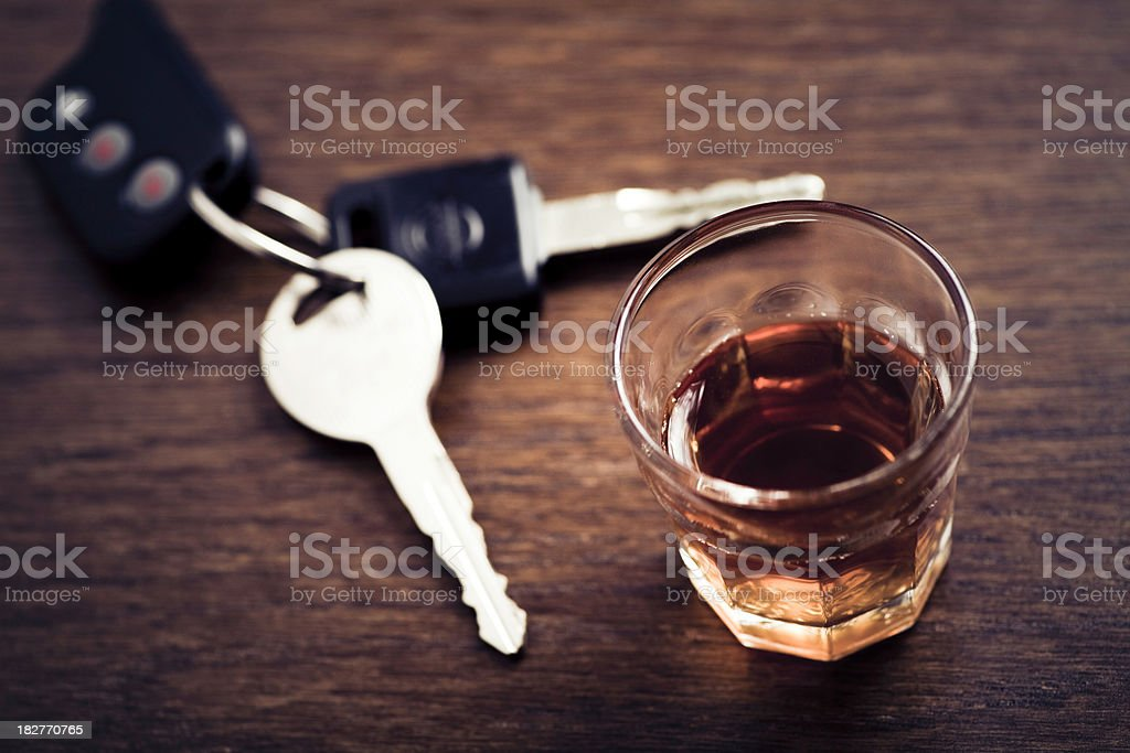 A glass of whisky and a set of car keys on a wooden table stock photo