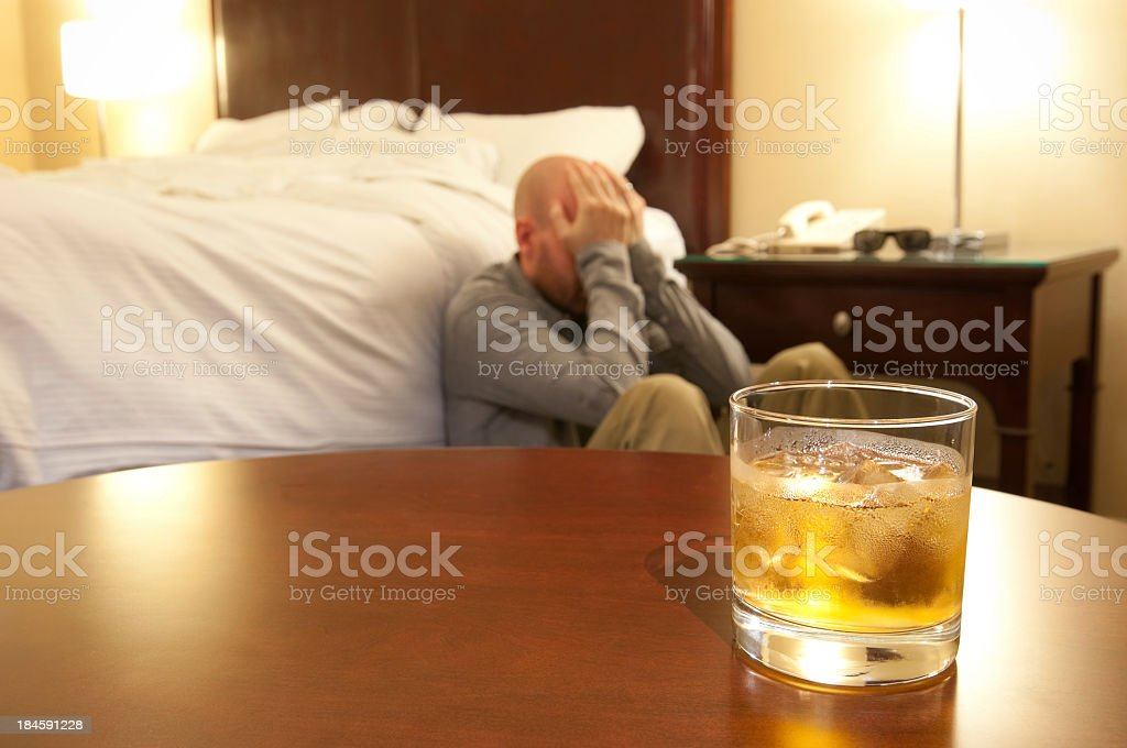 Glass of whisky and distraught man. royalty-free stock photo