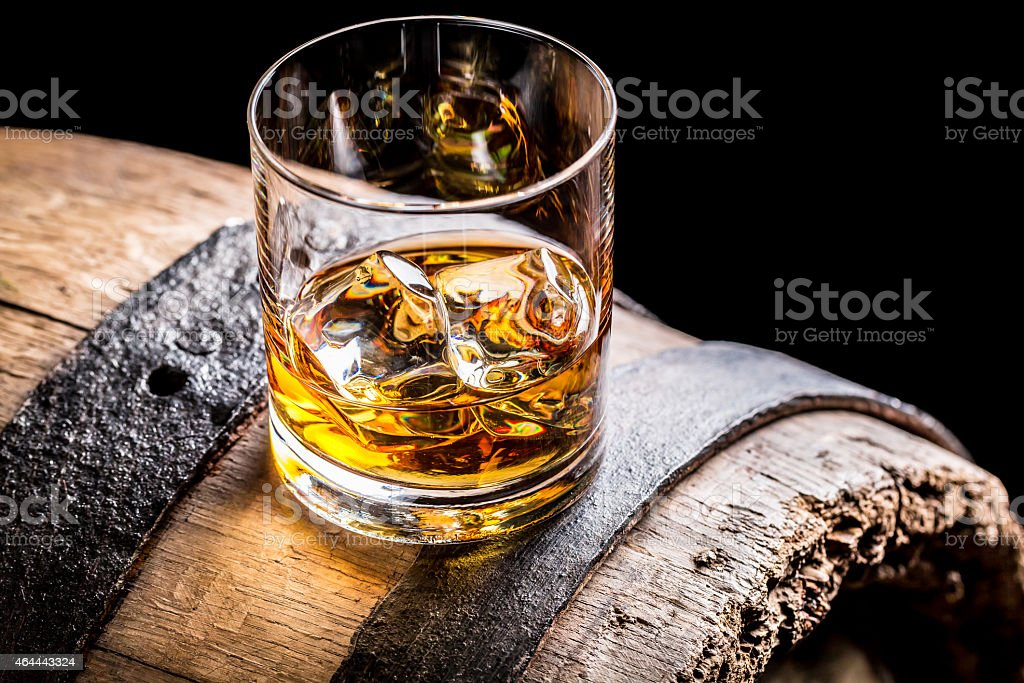 Glass of whisky and old wooden barrel stock photo