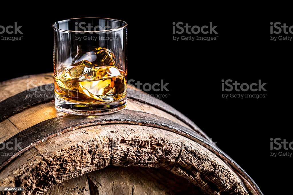 Glass of whisky with ice on old wooden barrel stock photo