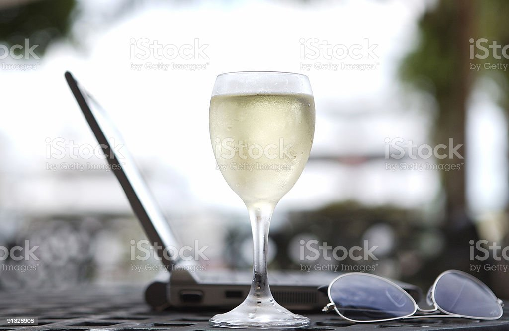 Glass of white wine and laptop. royalty-free stock photo