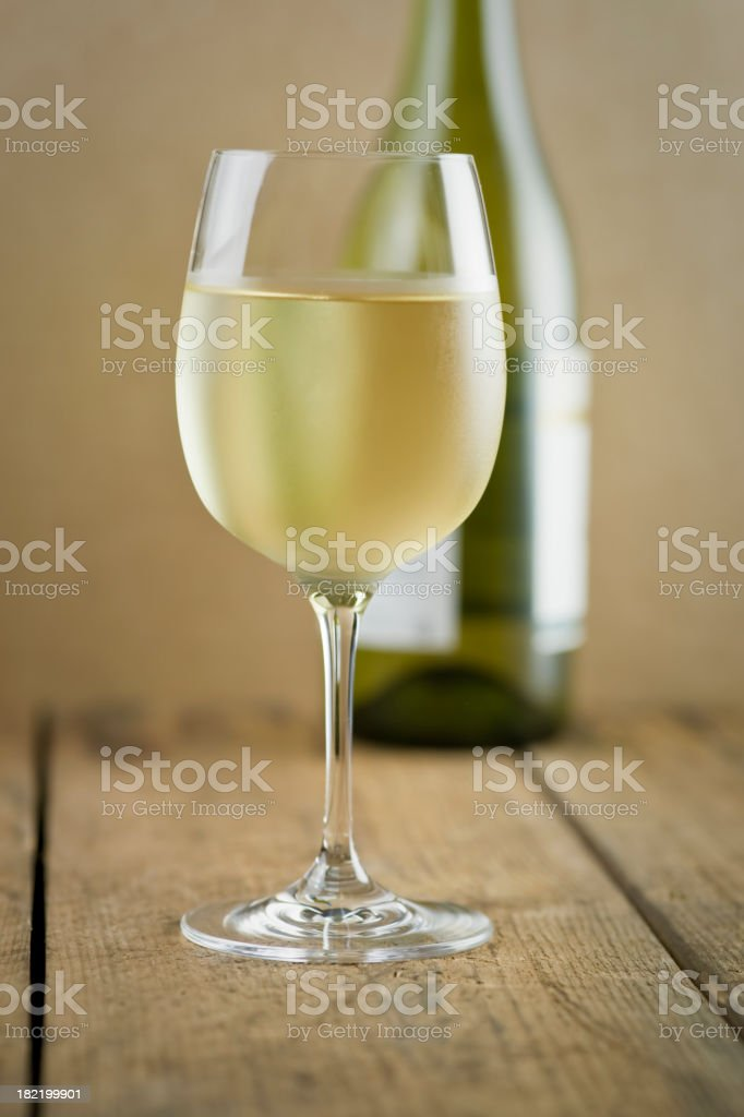 Glass of white wine, bottle and wood table stock photo