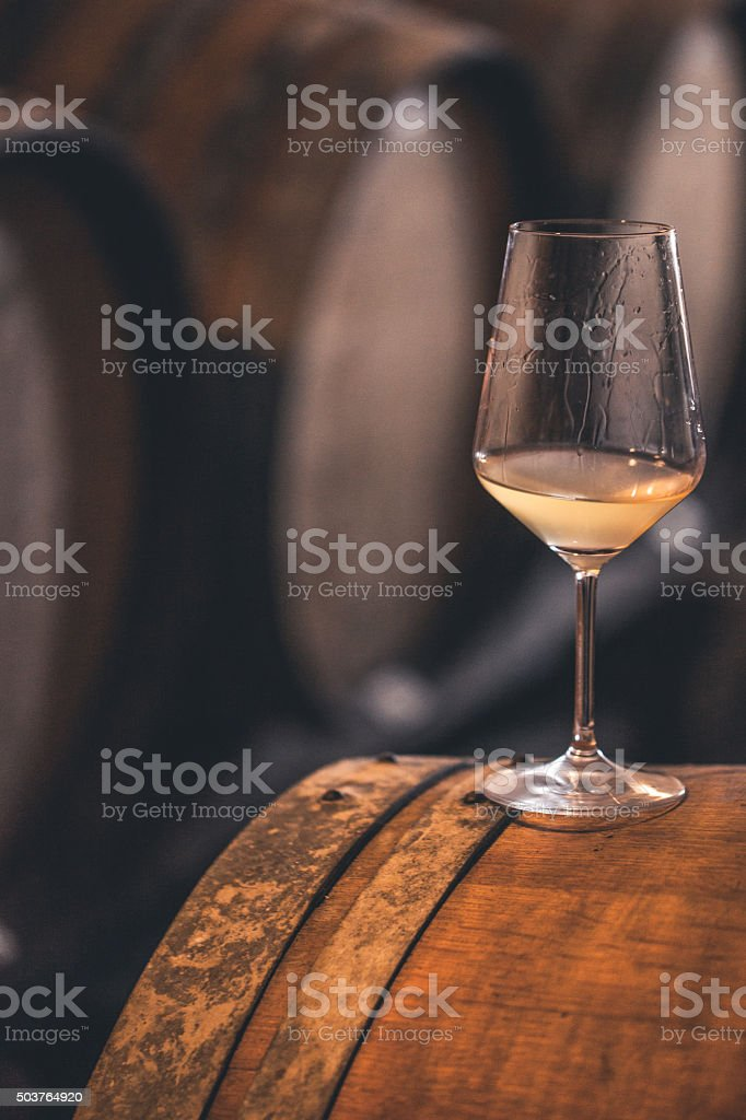 Glass of White Wine on a Barrel, Close-up stock photo