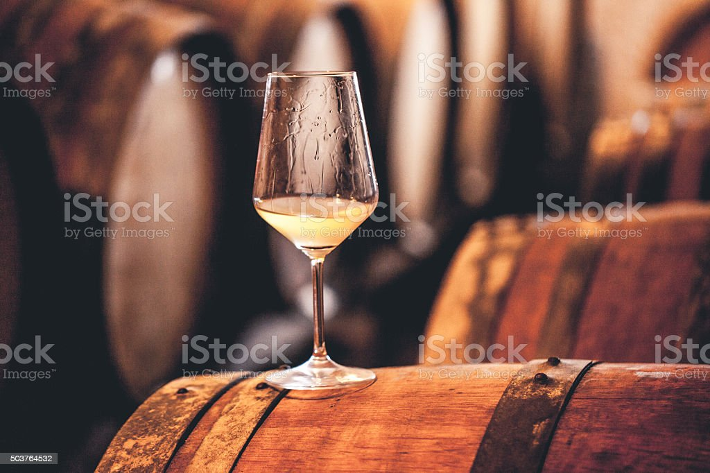 Glass of White Wine on a Barrel in Wine Cellar stock photo