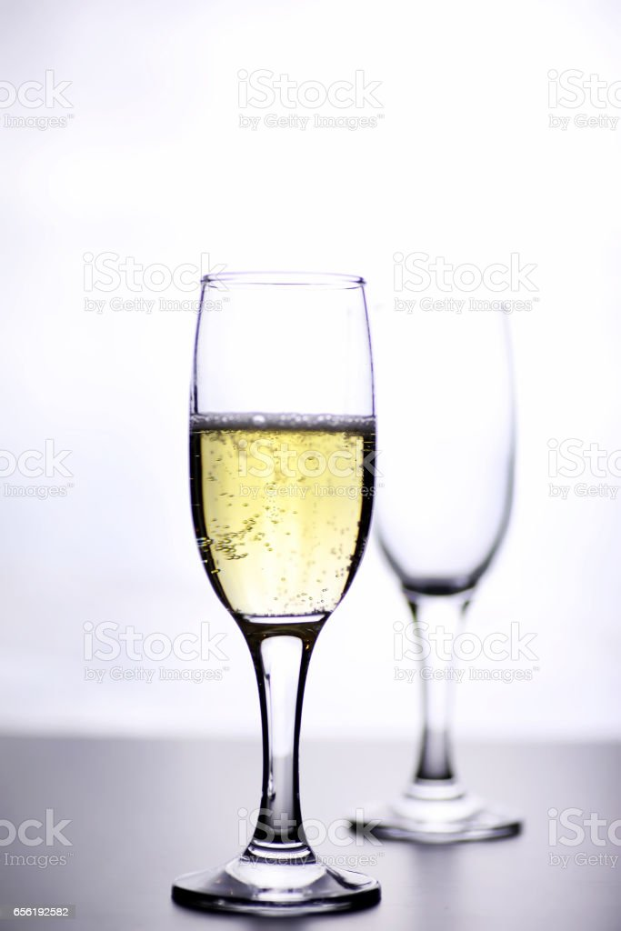 glass of white wine on a table on white background isolate stock photo