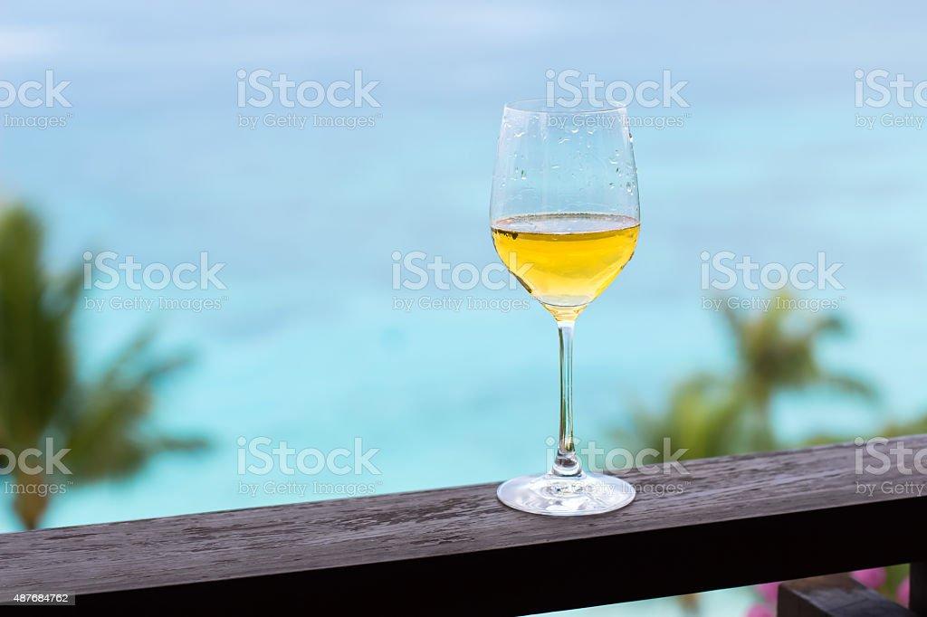 Glass of white wine on balcony rail stock photo