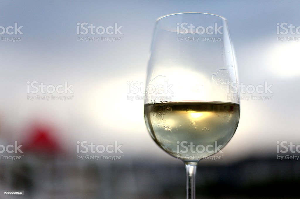 Glass of white wine on the sky background stock photo