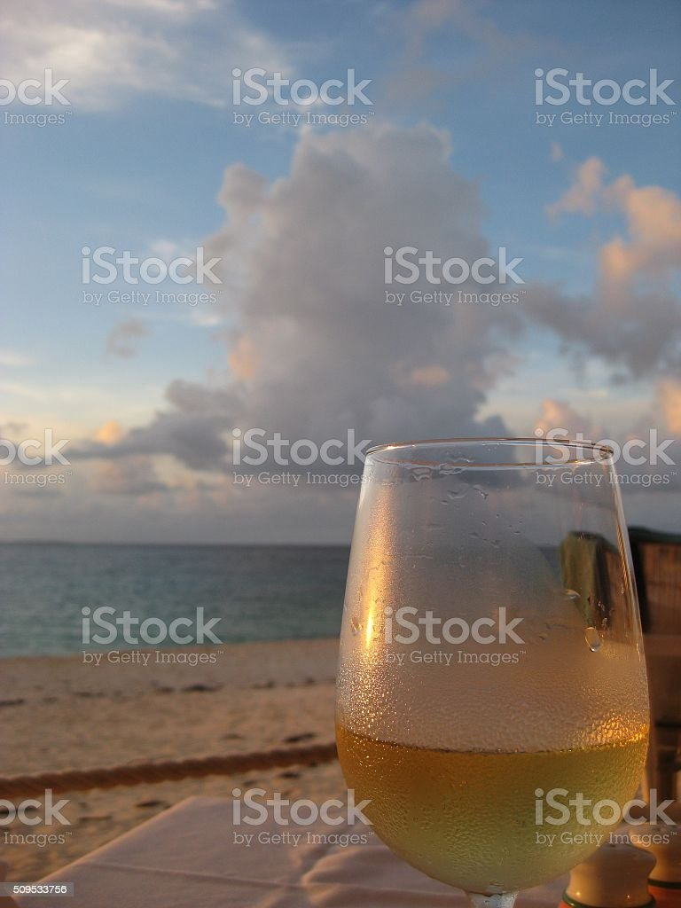 Glass of white wine sitting at the beach stock photo