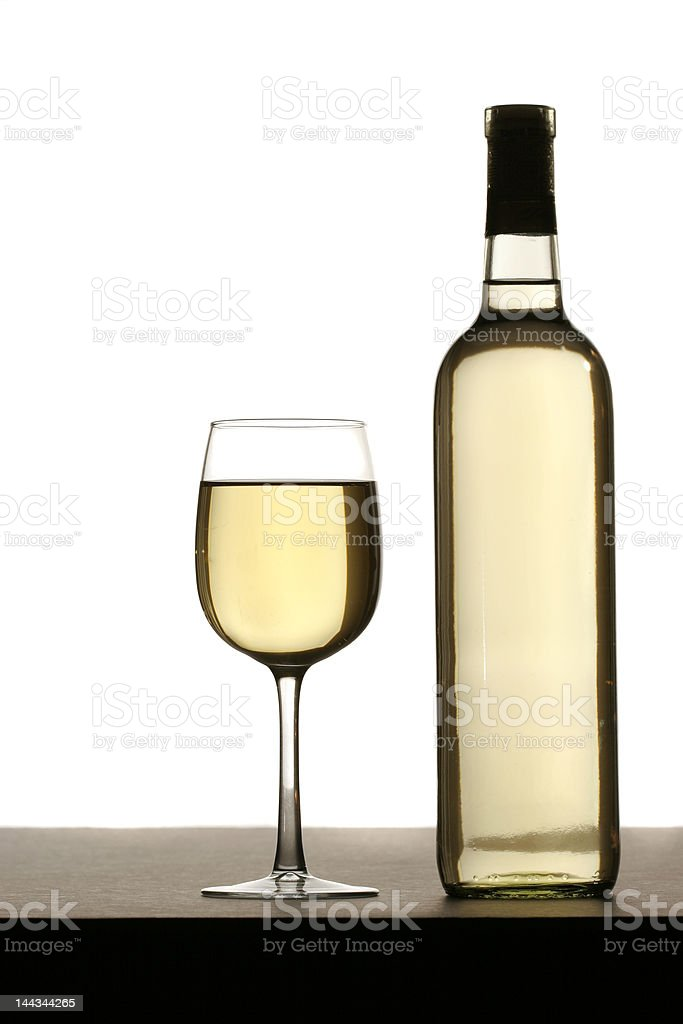 Glass of white wine with bottle on table, isolated royalty-free stock photo