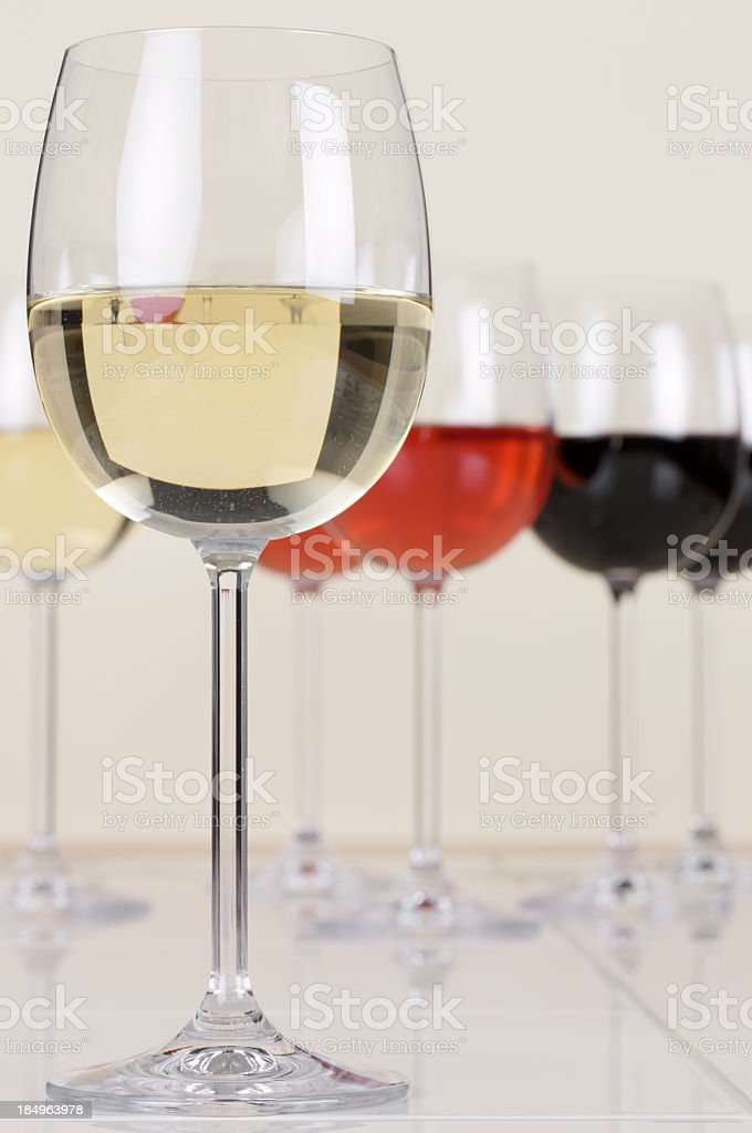 Glass of white wine with further glasses in the background royalty-free stock photo