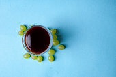 glass of wine and grapes, isolated on blue