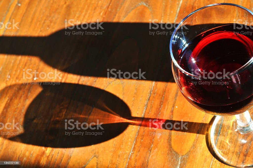 Glass of wine and shadow stock photo