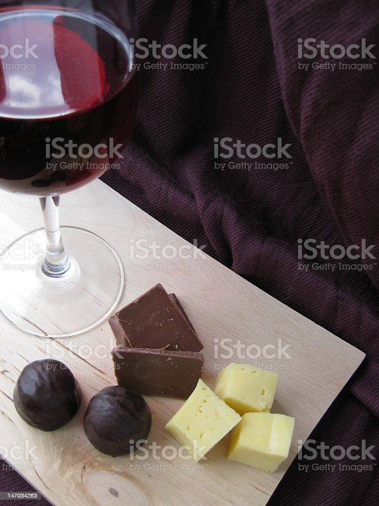 Glass of wine next to pieces of chocolate and cheese royalty-free stock photo
