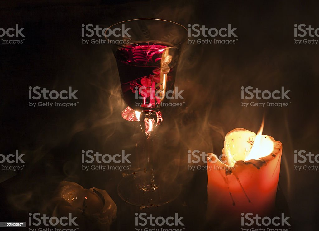 Glass of wine with candles in smoke royalty-free stock photo