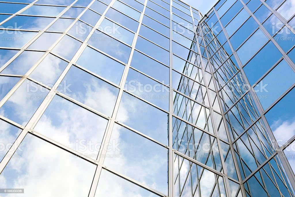 glass office facade reflects clouds and blue sky stock photo