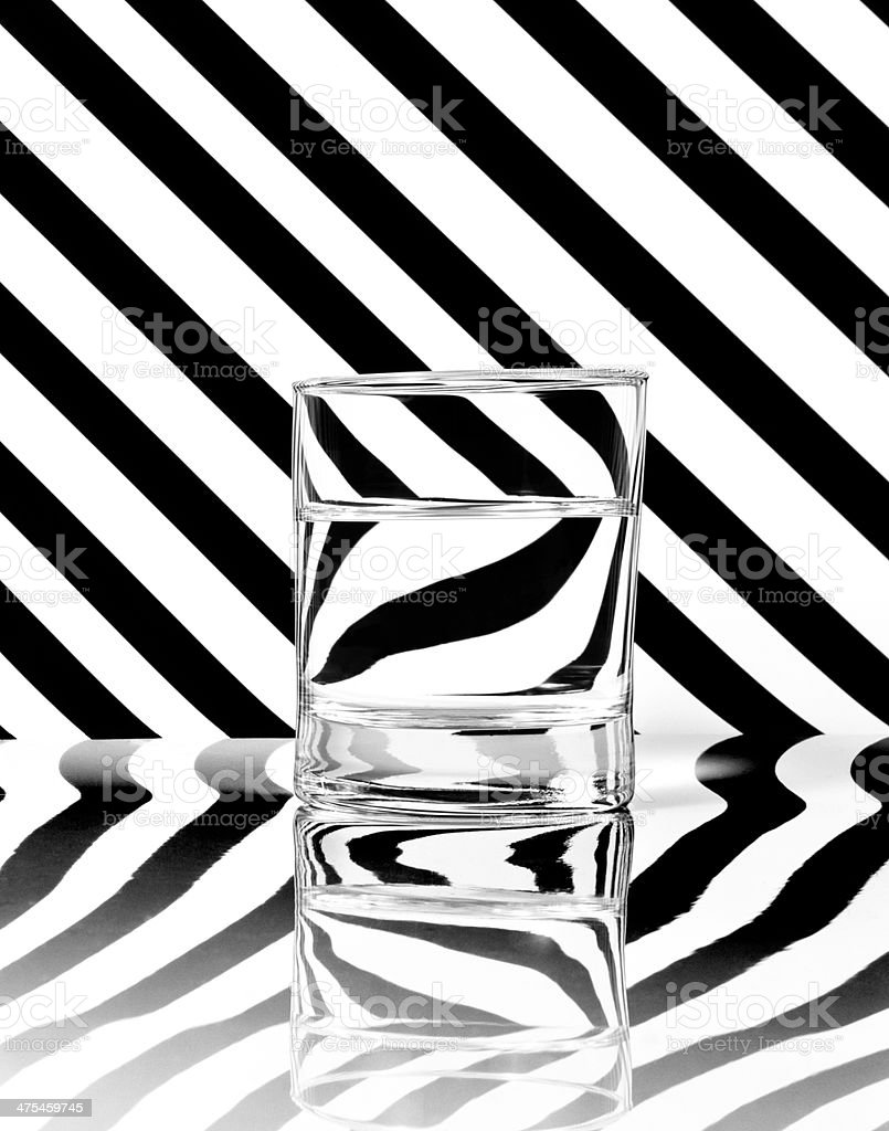 Glass on black and white stripes background stock photo