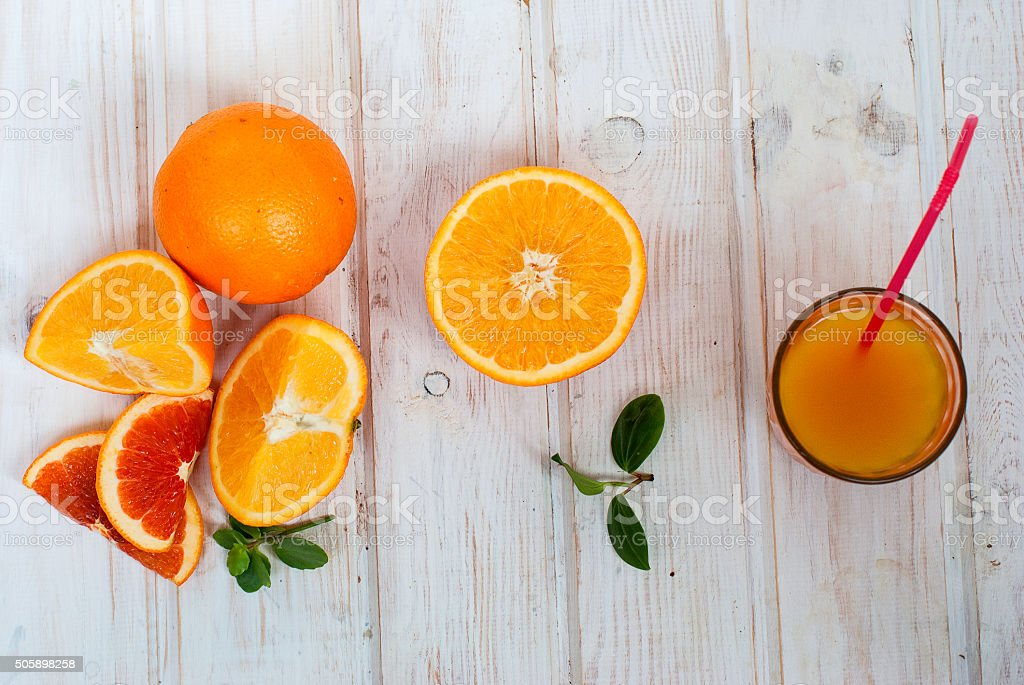 glass orange juice and a group oranges on white board stock photo
