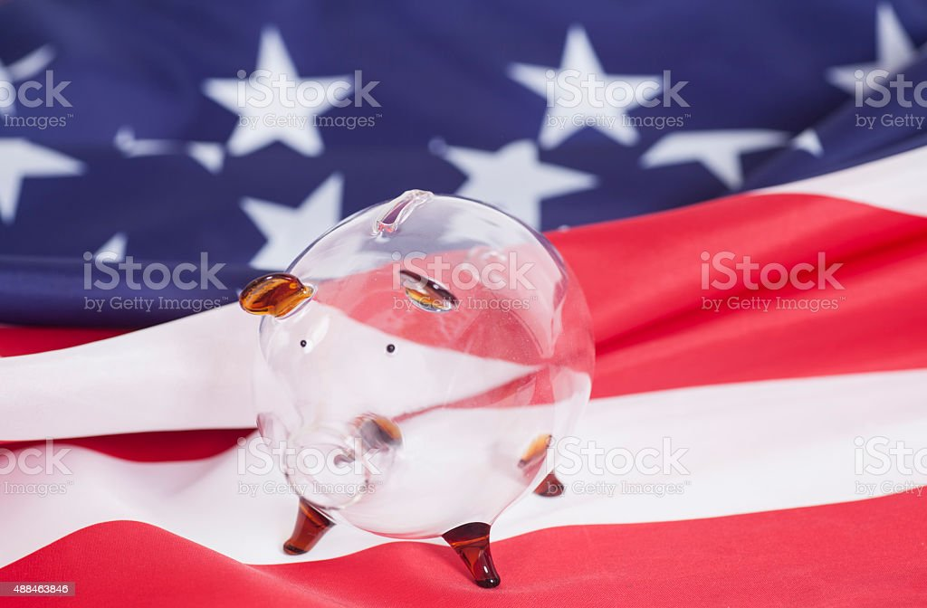 Glass Piggy bank against American national flag background stock photo