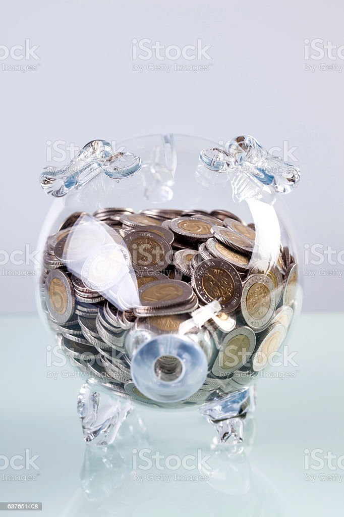 Glass piggy bank with coins inside stock photo
